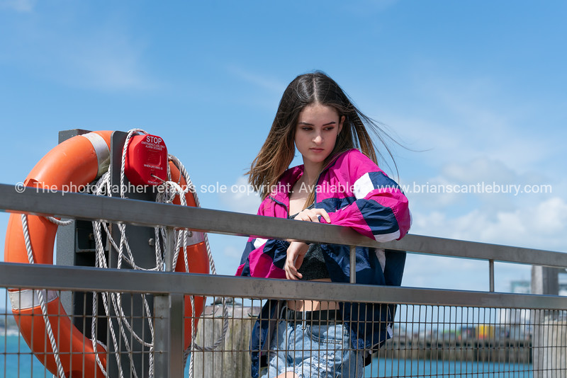 Attractive teenage woman stands leaning on waterfront railing next to orange life buoy. Model Released; Yes.