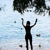Teenage girl stands by lake edge with ducks in water      Model Released; Yes