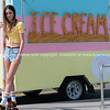 Pretty teenage girl stands on pavement wearing bright yellow modern top and old retro roller skates