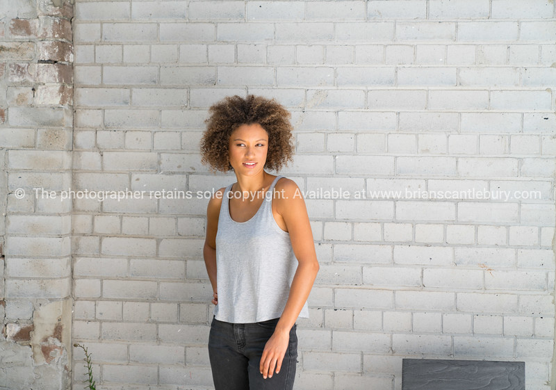 Beautiful Hispanic young woman standing by brick wall Model Released; Yes.
