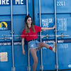 Pretty girl in red top and tatty denim shorts standing by cargo blue container     Model released; Yes.