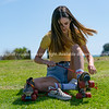 Pretty teenage girl in yellow top sits on grass putting retro style roller skates on