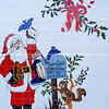 White tiled wall with image of Santa Claus alonside his letter box. Model Released; Yes.