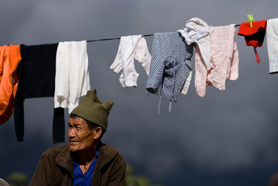 A local man in Darapani sitting by the laundry line at the guesthouse