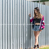 Modern teenage girl standing by corrugated iron fence background.      Model Released; Yes