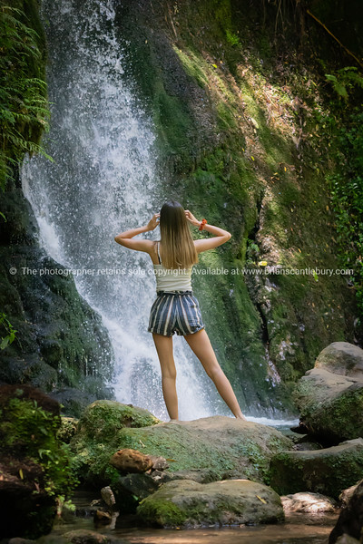 Young modern woman sitting on rock looking at McLaren Falls waterfall, Tauranga New Zealand. Model Released; Yes.      Model Released; Yes
