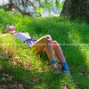 Teenage girl lying in green grass      Model Released; Yes