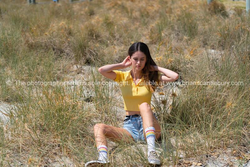 Teenage girl sitting in grass at beach