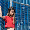 Looking bored, young woman in trendy clothes standing by industrial fence with blue  background.     Model released; Yes.