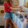 Young woman in red top checking through vintage vinyl records     Model released; Yes.