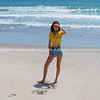 Attractive tall girl standing on beach casually with hand up shielding eyes from sun.
