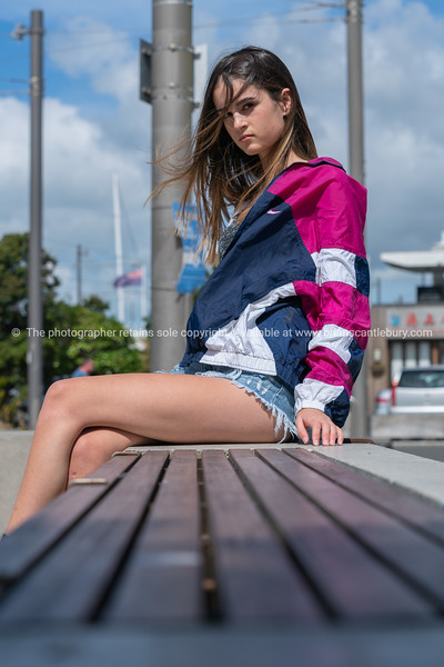 Teenage girl sitting on outdoor bench seat Model Released; Yes.