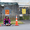 Teenager sitting bewteen road cones in front of no parking sign Model Released; Yes.