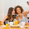 Young women at breakfast table Model Released; Yes.
