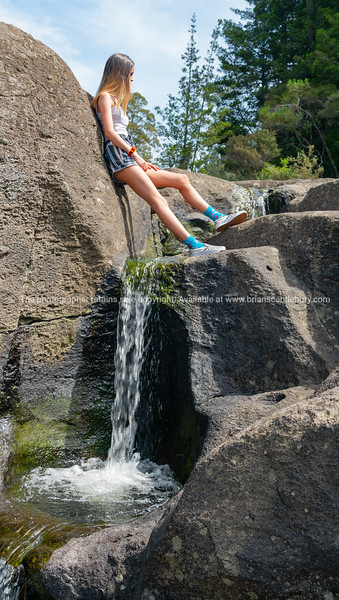 Low angle view girl standing leaning against large rock with water running below