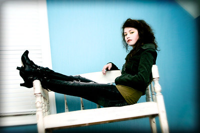Rhoda sitting on a white bench at an angle with her legs propped up.
