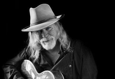 Black and white portrait of a middle aged Caucasian man with long hair and a white beard wearing a fedora hat while playing an electric guitar. Black background and sidelighting.