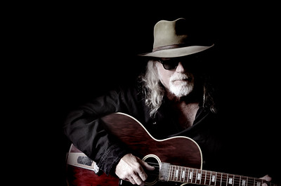 Middle-aged Caucasian man with long hair and a white beard wearing sunglasses, a hat and black shirt while holding a guitar. Black background and sidelighting. Vintage filter and desaturation applied