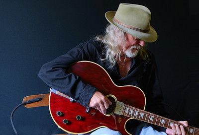Portrait of a middle aged Caucasian man with long hair and a white beard wearing  a fedora hat and a black shirt while playing an electric guitar. Dark background and sidelighting.