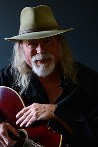 Portrait of a middle aged Caucasian man with long hair and a white beard wearing  a fedora hat and a black shirt while holding an electric guitar. Dark background and sidelighting.
