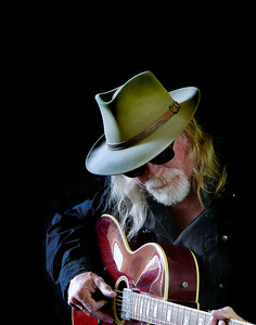 Portrait of a middle aged Caucasian man with long hair and a white beard wearing sunglasses, a fedora hat and a black shirt while playing an electric guitar. Black background and sidelighting.
