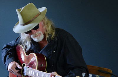 Portrait of a middle aged Caucasian man with long hair and a white beard wearing sunglasses, a fedora hat and a black shirt while playing an electric guitar. Dark background and sidelighting.