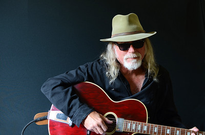 Portrait of a middle aged Caucasian man with long hair and a white beard wearing sunglasses, a fedora hat and a black shirt while holding an electric guitar. Dark background and sidelighting.