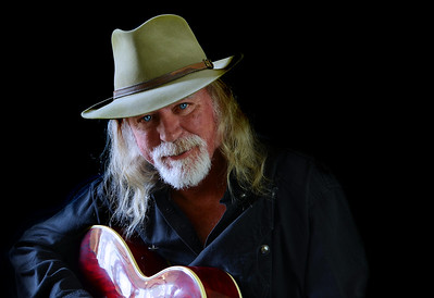 Portrait of a middle aged Caucasian man with long hair and a white beard wearing  a fedora hat and a black shirt while holding an electric guitar. Black background and sidelighting.