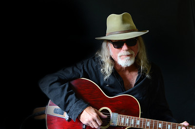 Portrait of a middle aged Caucasian man with long hair and a white beard wearing sunglasses, a fedora hat and a black shirt while holding an electric guitar. Black background and sidelighting.
