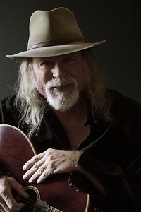 Middle-aged Caucasian man with long hair and a white beard wearing a fedora hat and black shirt while holding a guitar. Dark background and sidelighting. Vintage filter and desaturation applied