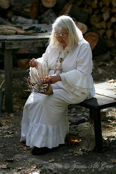 """Julia Parker, b. 1929, has demonstrated basket weaving to visitors in Yosemite Valley's Miwok Indian Village/Museum since 1960 and today is acknowledged possibly as California's best maker of baskets. She has been featured in books, films, museum exhibits and a solo gallery exhibit and has had baskets placed in collections around the world including Queen Elizabeth II of England. She is one of the few people living today who was taught by the great basket weavers of the Yosemite Indian Field Days (weavers largely born in the mid 19th century, learned in a traditional manner and pushed the art to its extreme refined states). Julia says: """" The old people taught us take from the earth, give back to the earth, and never forget to say please and thank you."""" She has worked to protect the native plants from invasive species and development."""
