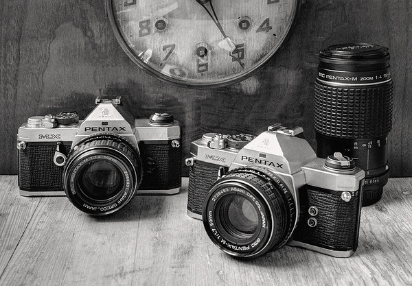 Two Pentax MX 35mm film cameras and a Pentax 75-150mm zoom lens, all from late 1970s - early 1980s. (HDR + grain and contrast)