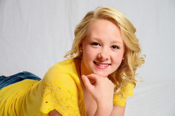 Senior portrait of girl in yellow shirt laying on belly