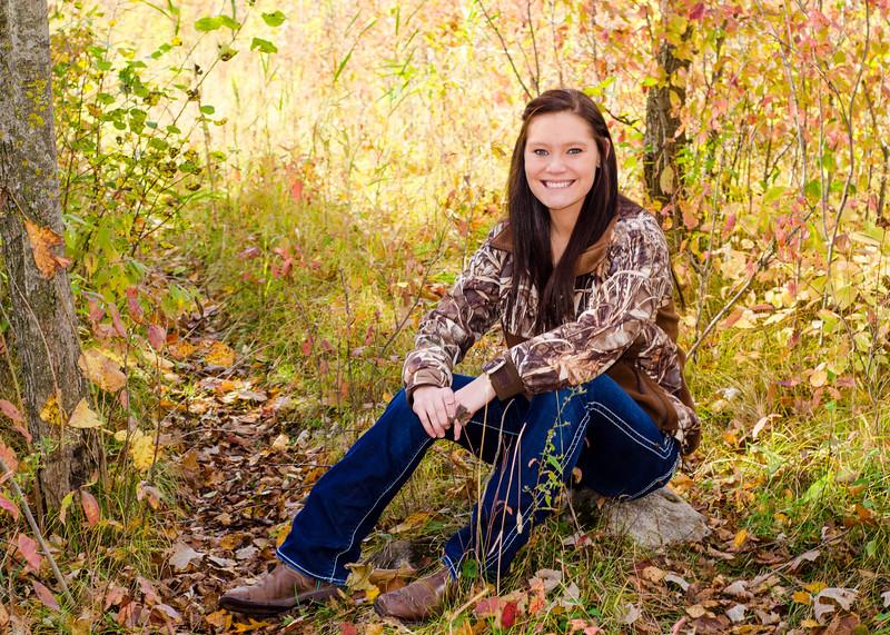 senior portrait of girl sitting on rock in woods