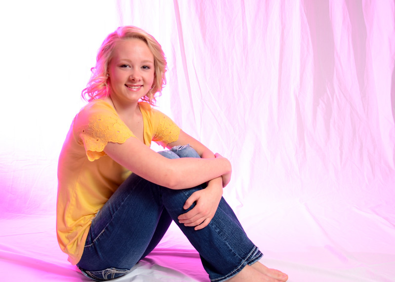 senior portrait of girl in yellow shirt with pink lighting