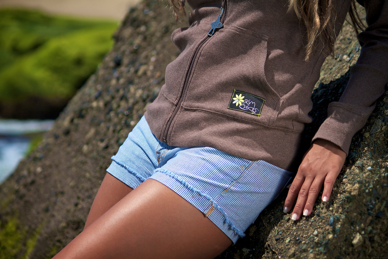 Closeup of Silvia wearing the Skim Chicks brown zippered sweater and pin striped denim shorts.