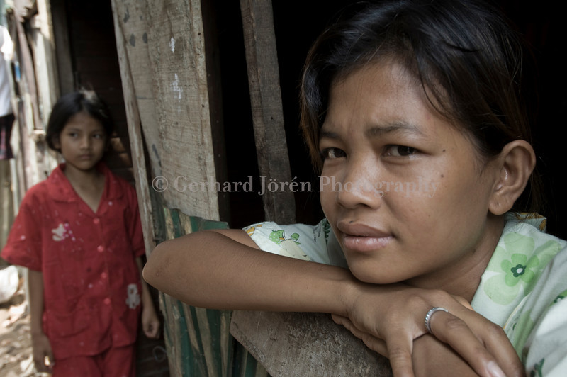 Cambodia. A young sex worker and her younger sister at their home in a slum ...