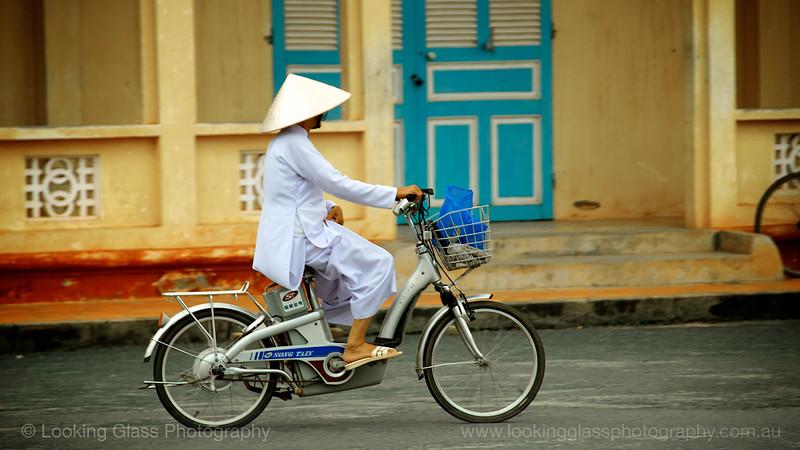 Nun riding outside Cao Dai Temple