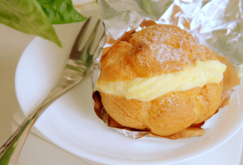 File No.61<br /> <br /> めぐり廻って、シュークリーム。<br /> <br /> エルサレムの市場にアメリカ系ユダヤ人のケーキ屋が一軒、あった。まるで師走のデパ地下みたいにごったがえす安息日前の金曜の午後、ショーケースの片隅にシュークリーム。なんて、いやいや、カスタードのお菓子なんて、ほとんどエルサレムでは唯一無二に近い。久しぶりに出会ったシュークリームさまにワクワクしながら、だけどそれはあっけない夢の終り。ゴワゴワブツブツ、このカスタード、失敗作でしょ・・・と、日本だったら到底ショーケースに並ぶことなんてない代物だった。<br /> <br /> ところ変わって、クロアチア。ここではシュークリームさまは「プリンセス・クラフナ」なんて愛らしい名の、国民的お菓子。たいていのケーキ屋にあった。4年ほど住んだザグレブの、ヴィンツクというかつての老舗ケーキ屋のそれは、やっぱりドイツ・オーストリア文化圏だなあ。あまりのクリームの多さに、ひとつまるまる完食すればもれなく胃もたれに苦しむというおまけつき。<br /> <br /> いちばん美味しかった記憶は、南クロアチア。スプリットという、なんともロマンチックな古代ローマ皇帝の宮殿跡の町のプリンセス・クラフナは、イタリア文化が入り交じりっているせいでか、クリームが滑らかでどれもそこそこの味だった。が、しかし、クロアチアのお店はなんといっても味が一定しない。毎回同じクオリティなんて至難の業。けっきょくしばらくするともういいやって。<br /> <br /> そして、京都。大宮花屋町を少し上がったところ。昭和七年ぐらいから続いているらしいパン屋「きんまつどう」。ほんとは金の松の堂で「キンショウドウ」というらしいが、その界隈で育ったヒゲ玉ノ母はなぜかいつも「きんまつどう」。パンはもちろん、ここのシュークリームさまがいやいや、うまい。しっかりしたシュー生地に、子供時代にタイムスリップ。今はもうなくなってしまった、金沢のオリヤンタルというケーキ屋の味に似ている気がする。<br /> <br /> ああ、いいなあ、こういうのって。なんだか地球をあちこち歩き回って、けっきょくここだった、みたいな、ね。