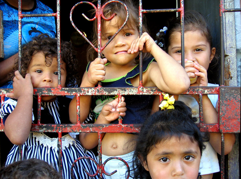 A family of Nicaraguan illegal immigrants in a San Jose, Costa Rica, shanty town cling to their front gate.  Nicaraguan immigrants serve a very similar social and economic role in Costa Rica as Mexicans do to the United States.  They help keep the Costa Rican economy afloat by providing cheap labor for work that Costa Ricans are not willing to do and they serve as a general social scapegoat.  The reality is that Nicaraguan illegals live dangerous and unhealthy lives in adjunct poverty in the attempts of making a living for themselves and family members remaining in Nicaragua.  Nicaraguans need work and the Costa Rican economy needs hard workers to fill their many available agricultural and industrial jobs.  These neighbors should cooperate to help one where the other lacks, but instead they fight a constant battle of racist politics whose victims are children and families like the ones in this photo above.