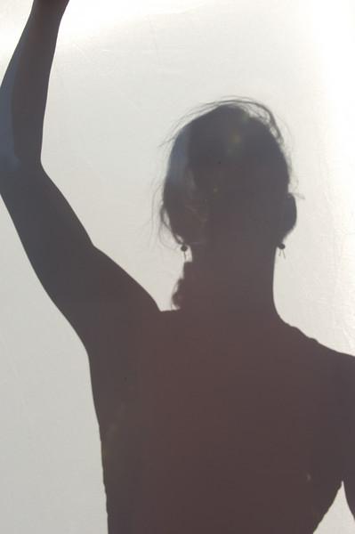 The mystery model Molly Loomis Tyson behind a sunlit curtain