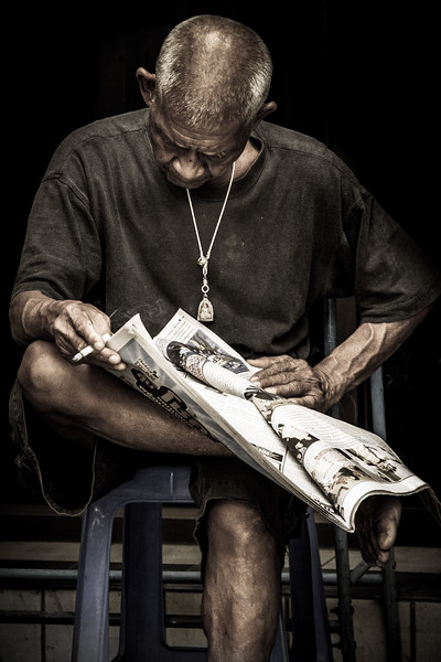 Nice portrait of an old man reading the news.