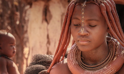 Portrait of a Young Woman and child in Himba Tribal Village in Namibia.