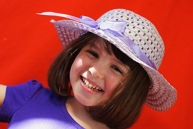 Keep or delete?? : I came home to find her dancing around the house in her new hat. I looked around for a good place to take a shot of her and then I noticed the the sun was shinning into the kitchen. I quickly grabbed a red blanket and hung it over the kitchen cabinets. I had her stand in the sunlight the fired away. My wife isn't too impressed with this shot which has me 2nd guessing myself...any thoughts would be gladly appreciated!!!