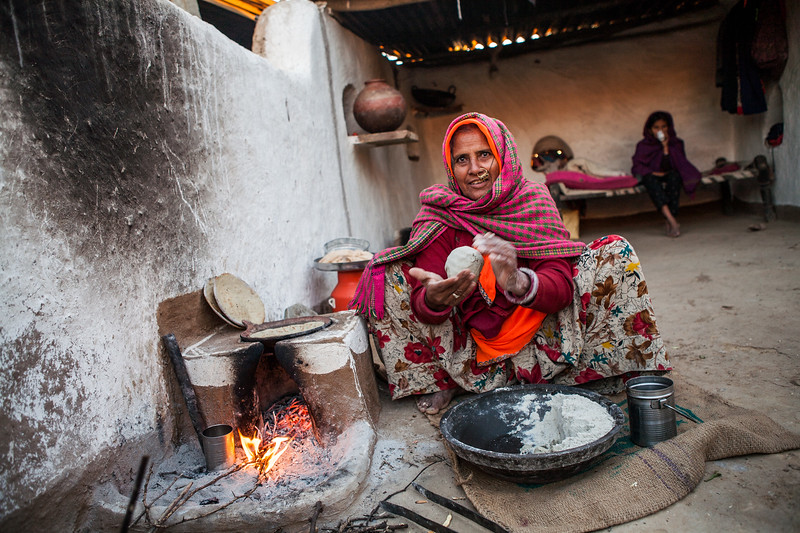Tulsa making bajra rotis in her home in the village of Jaipura in Rajasthan, India