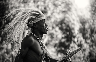A young male Rwandan is performing a cultural dance, wearing a traditional tribal headdress and beaded ornaments.