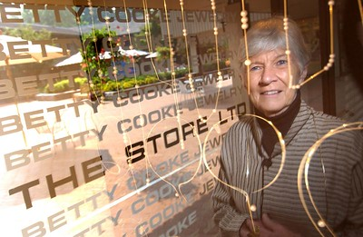 Betty Cooke, Owner of The Store LTD at Cross Keys for 40 years. Here she is shown reflecting in a display case of her designer Jewelry with thier lindow logo showing in the background. MF-D 8/12/05. Credit- The Daily Record