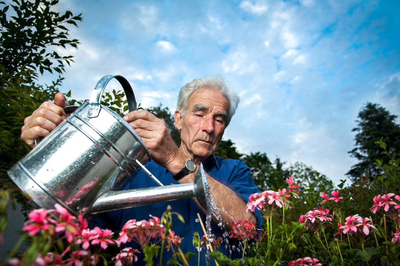 Senior watering his flowers and looking happy