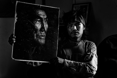 William Sam holds up a portrait of his Grandfather, the strong Gwich'in leader Moses Sam.