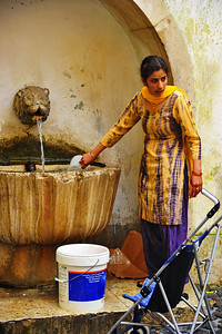 A woman rinsing her laundry at the local drinking fountain